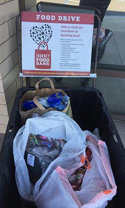 A Food Drive Sign With A Heart & Bags Of Food Placed In A Plastic Bin