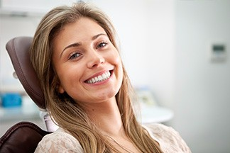 woman sitting in chair in orthodontic office smiling