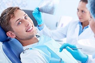 Blue Eyed Man Sitting In Orthodontist Chair Smiling